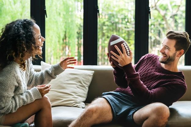 Par jovem, observar, futebol americano, casa