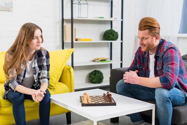 Par jovem, olhando um ao outro, com, tabuleiro xadrez, branco, tabela