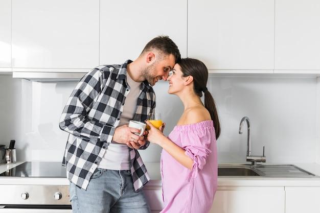 Par jovem, olhando um ao outro, segurando, xícara café, e, suco, vidro, em, cozinha