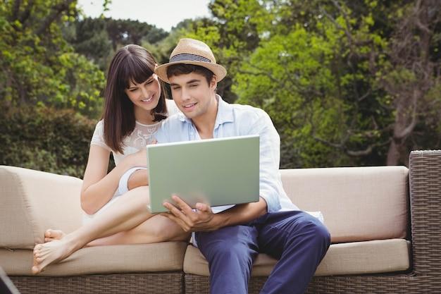 Par jovem, olhar, laptop, enquanto, sentando, ao ar livre, ligado, sofá