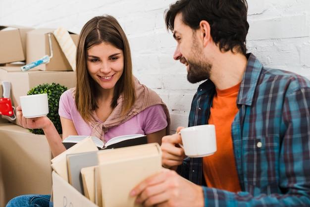 Par jovem, olhar, livros, em, caixa papelão, segurando, xícaras café, em, mão