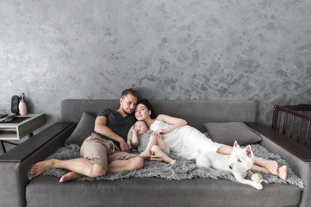 Par jovem, relaxante, ligado, sofá, com, seu, filho, e, cachorro branco