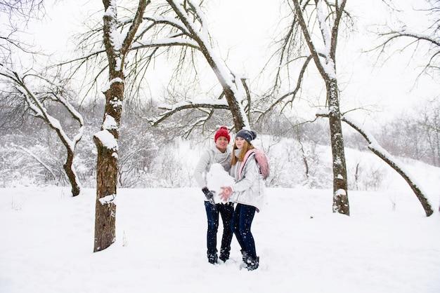 Par jovem, segurando bola neve