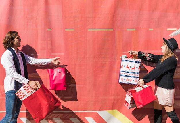 Par jovem, segurando, bolsas para compras