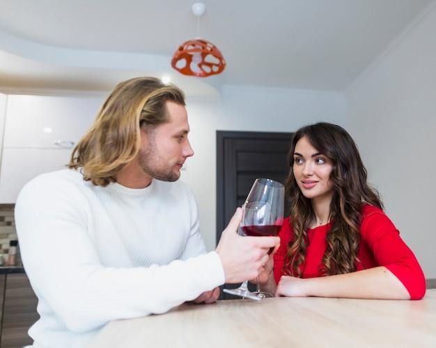 Par jovem, sentando, casa, brindar, wineglasses