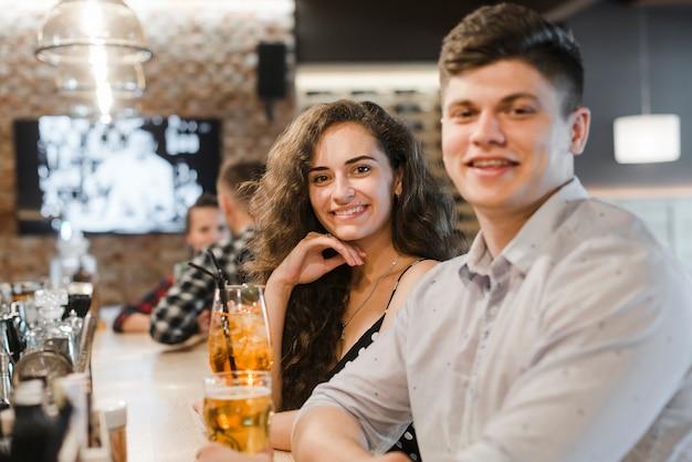Par jovem, sentando, em, restaurante, desfrutando, bebidas