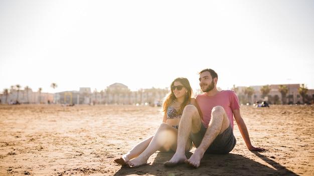 Par jovem, sentando, junto, praia arenosa