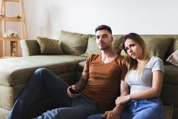 Par jovem, sentando, perto, a, sofá, olhando televisão, casa