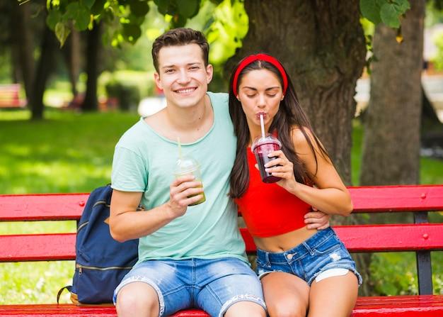 Par jovem, sentar-se banco, bebendo, smoothies saudáveis, parque