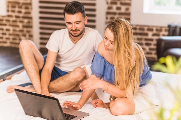 Par jovem, sentar-se cama, usando computador portátil