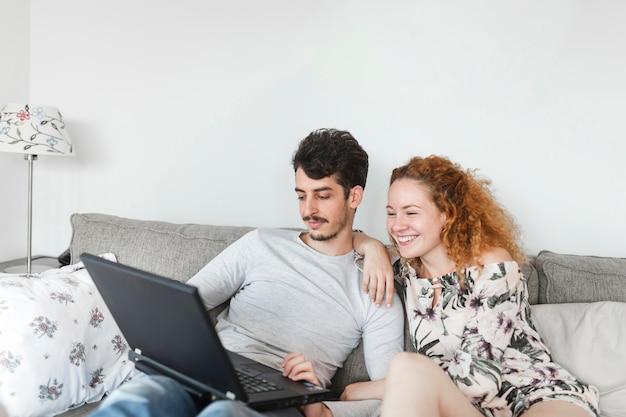 Par jovem, sentar sofá, com, laptop