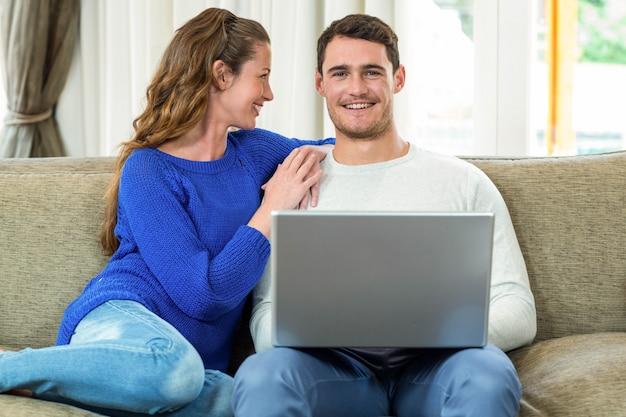 Par jovem, sorrindo, cara enfrentar, ligado, sofá, e, usando computador portátil, em, sala de estar