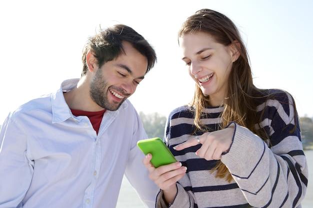 Par jovem, sorrindo, e, olhando telefone móvel