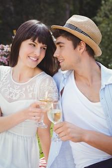 Par jovem, sorrindo, e, tendo, vidro vinho, em, jardim