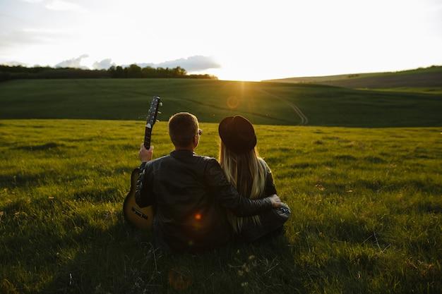 Par jovem, tendo divertimento, em, um, pôr do sol, sob, a, guitarra, canção