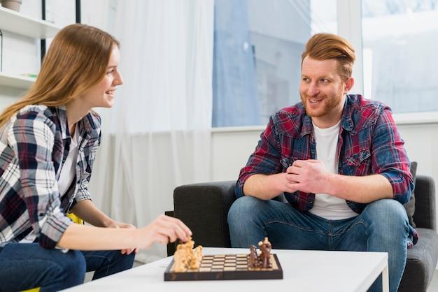 Par jovem, tocando, a, tabuleiro de xadrez, em, a, sala de estar, casa