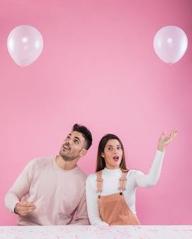 Par jovem, tocando, com, balões brancos