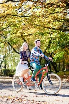Par jovem turista, homem barbudo bonito e mulher atraente, andar de bicicleta juntos