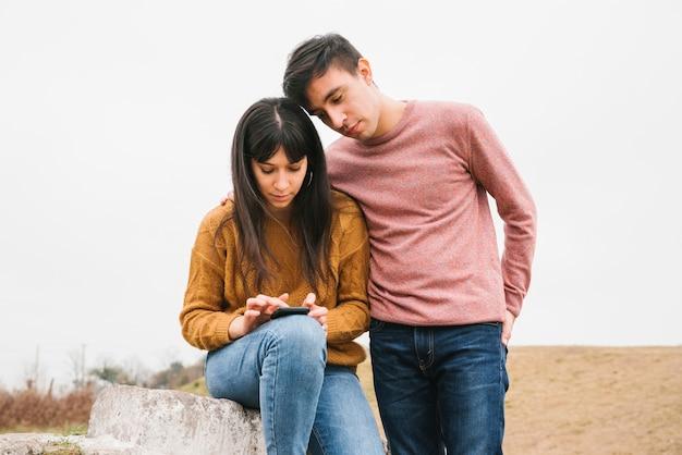 Par jovem, usando, smartphone, em, natureza