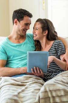 Par jovem, usando, tablete digital, ligado, sofá, casa