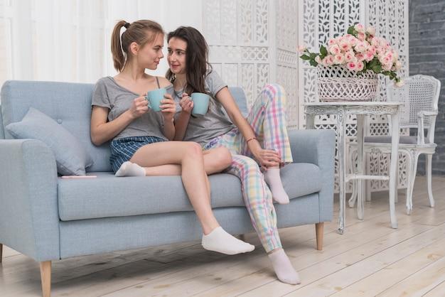 Par lésbico, segurando, xícara café, sentar sofá, olhando um ao outro