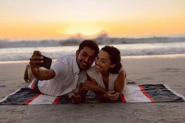 Par, levando, selfie, com, telefone móvel, praia