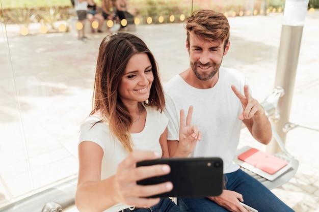 Par, levando, um, selfie, e, mostrando, sinal paz