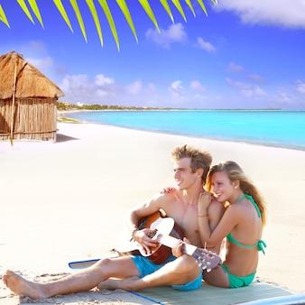 Par louro, sentando, em, um, praia, areia, violão jogo