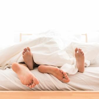 Par, mentindo, descalço, cama