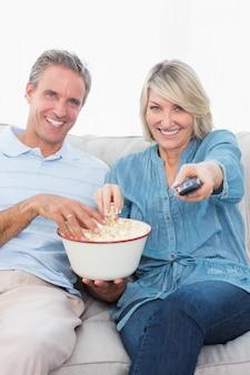 Par, olhando tv, e, comendo pipoca, sofá