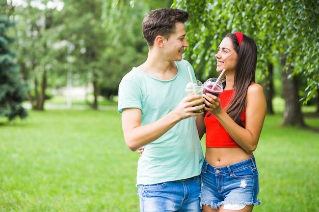 Par, olhando um ao outro, brindar, smoothies, parque