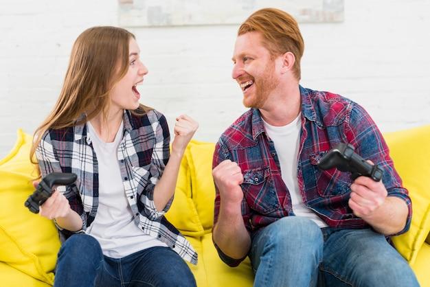 Par, olhando um ao outro, clenching, seu, punho, após, ganhar, a, videogame