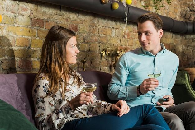 Par, olhando um ao outro, segurando, bebidas