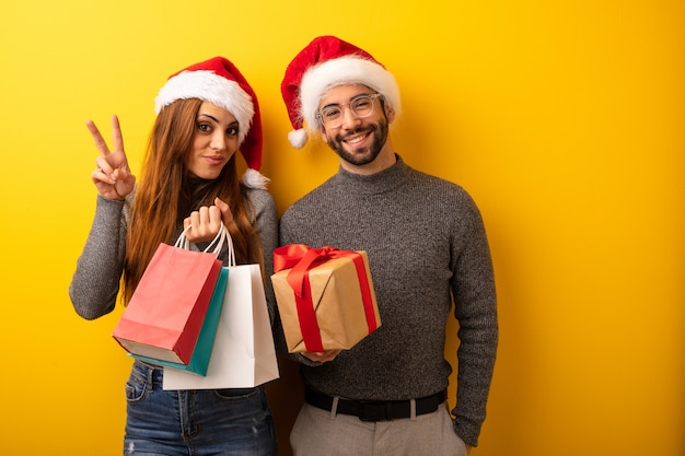 Par, ou, amigos, segurando, presentes, e, bolsas fazendo, mostrando, numere dois