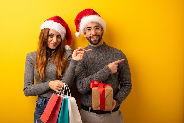 Par, ou, amigos, segurando, presentes, e, bolsas para compras, apontar, ao lado, com, dedo