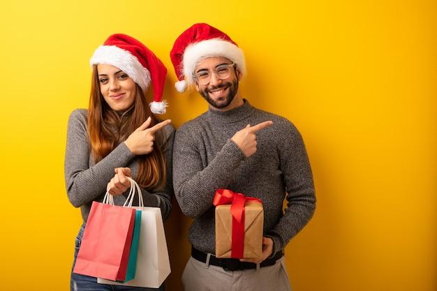 Par, ou, amigos, segurando, presentes, e, bolsas para compras, sorrindo, e, apontar, ao lado