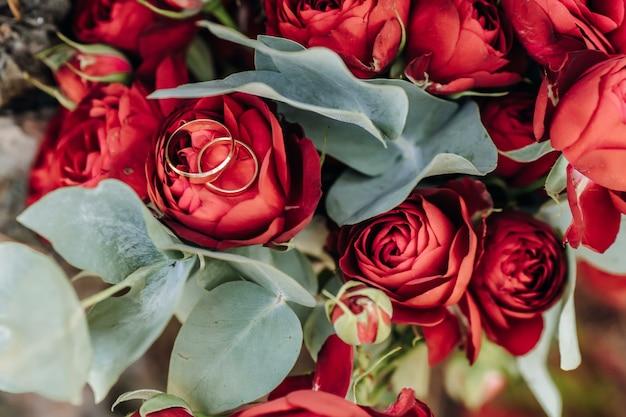 Par ou anéis de casamento em flores de buquê com foco em anéis
