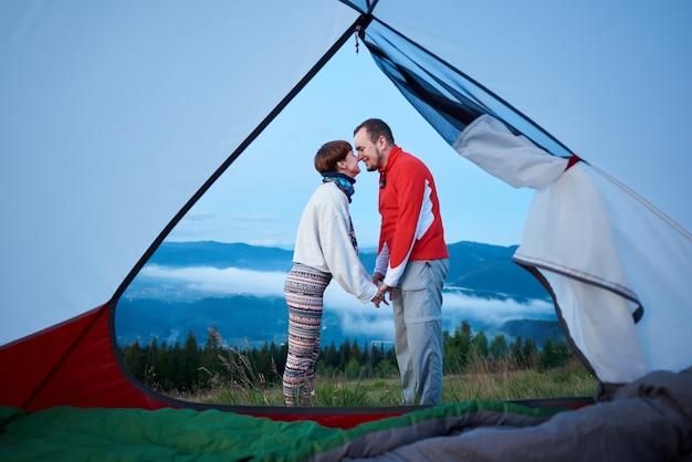 Par romântico aprecia um ao outro, de mãos dadas no fundo uma bela paisagem de montanhas e o céu brilhante da manhã ao amanhecer. vista de dentro de uma barraca