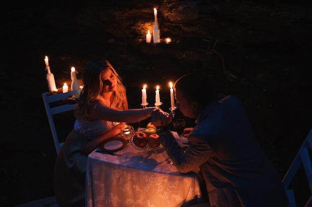 Par romântico de mãos dadas juntos sobre velas
