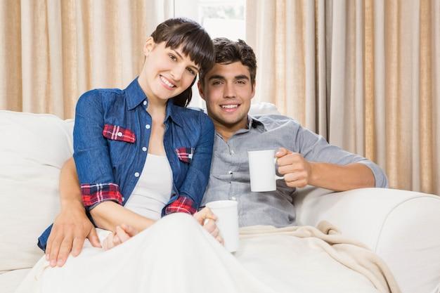 Par romântico em casa relaxando no sofá tomando café