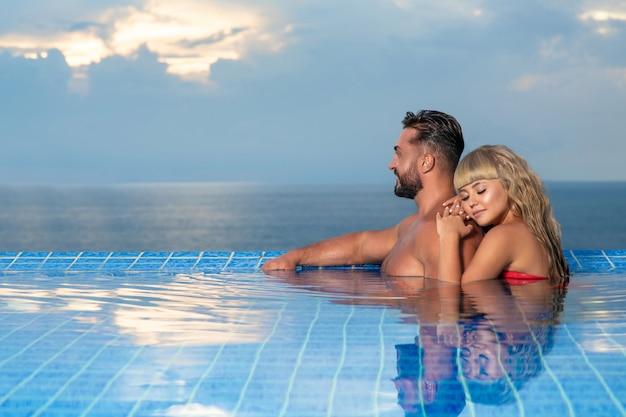 Par romântico: homem loiro e brutal estão relaxando juntos na piscina infinita