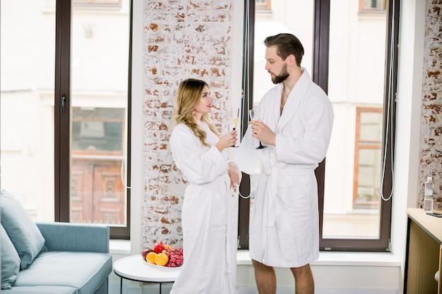 Par romântico junto com taças de champanhe no quarto do hotel
