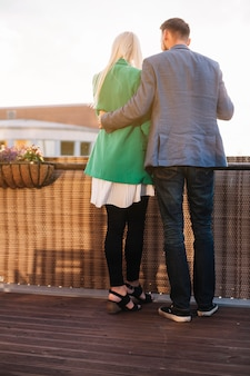 Par romântico, segurando, copos de vinho, ficar, em, sacada, olhando um ao outro