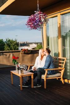 Par romântico, sentar telhado, beijando um ao outro