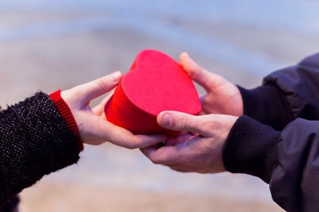 Par, segurando, caixa presente presente, em, forma coração