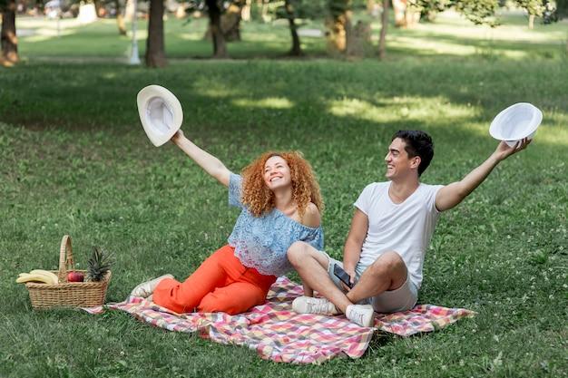 Par, segurando, chapéus, cima, parque