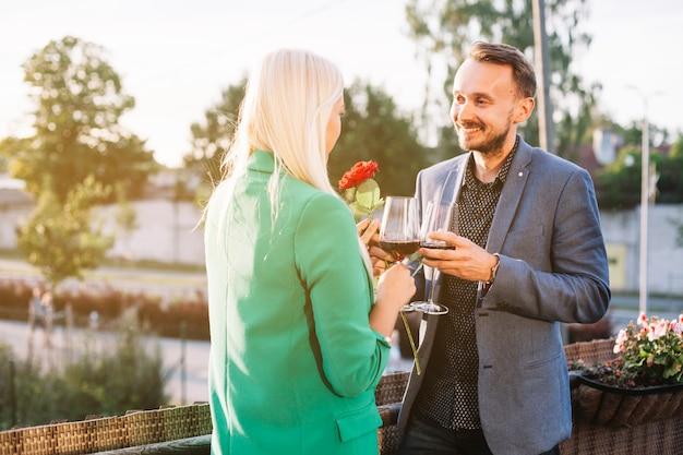 Par, segurando, copos de vinho, beijando, um ao outro, em, ao ar livre