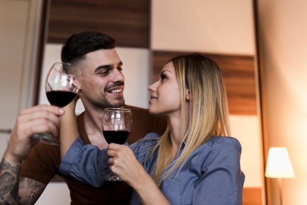 Par, segurando, copos de vinho, olhando um ao outro