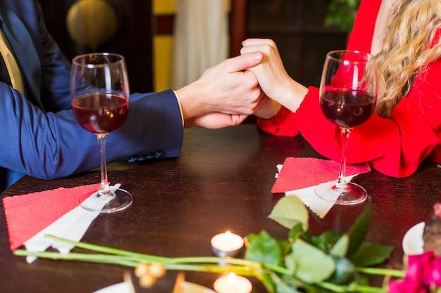 Par, segurando, mãos, em, tabela madeira, em, restaurante