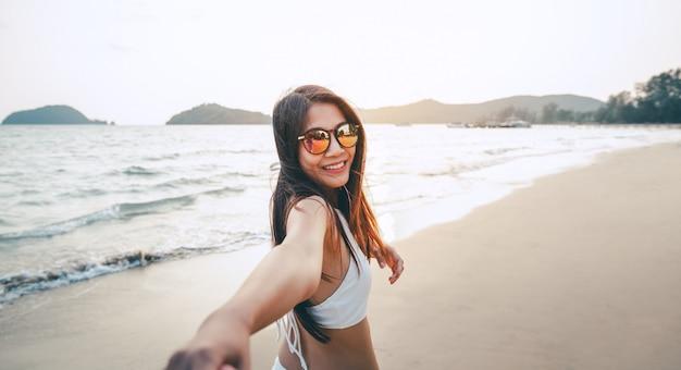 Par, segurando, mãos, praia, pôr do sol